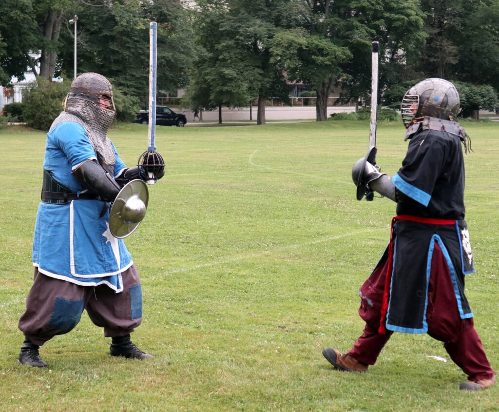 Two fighters, wearing medieval garb and metal helmets, prepare to battle. They are wielding swords made of rattan wrapped with duct tape.